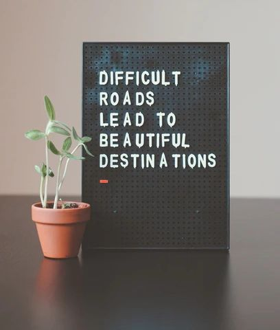 A sign depicting the words difficult roads lead to beautiful destinations on the future self blog post page