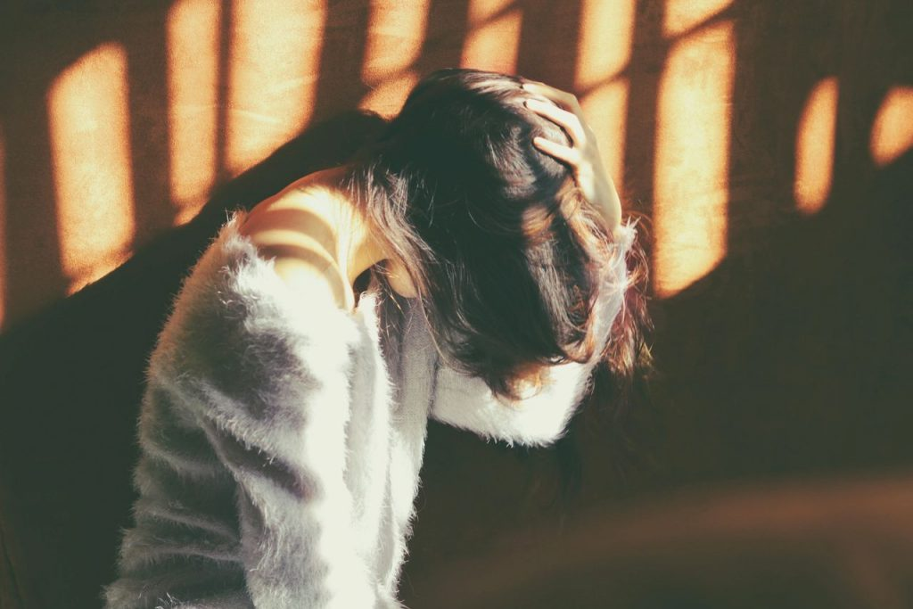 A woman in scattered sunlight, symbolically asking 'Is my anxiety normal?'