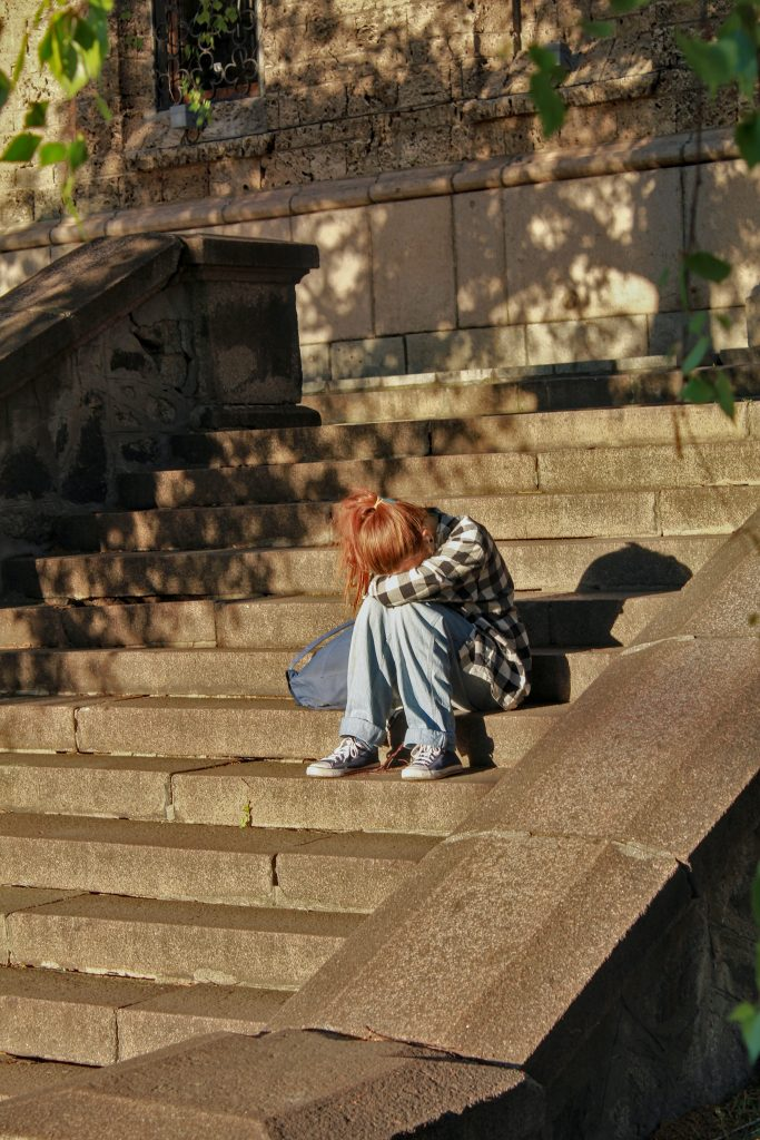 A woman sitting on steps, dealing with either anxiety or depression.